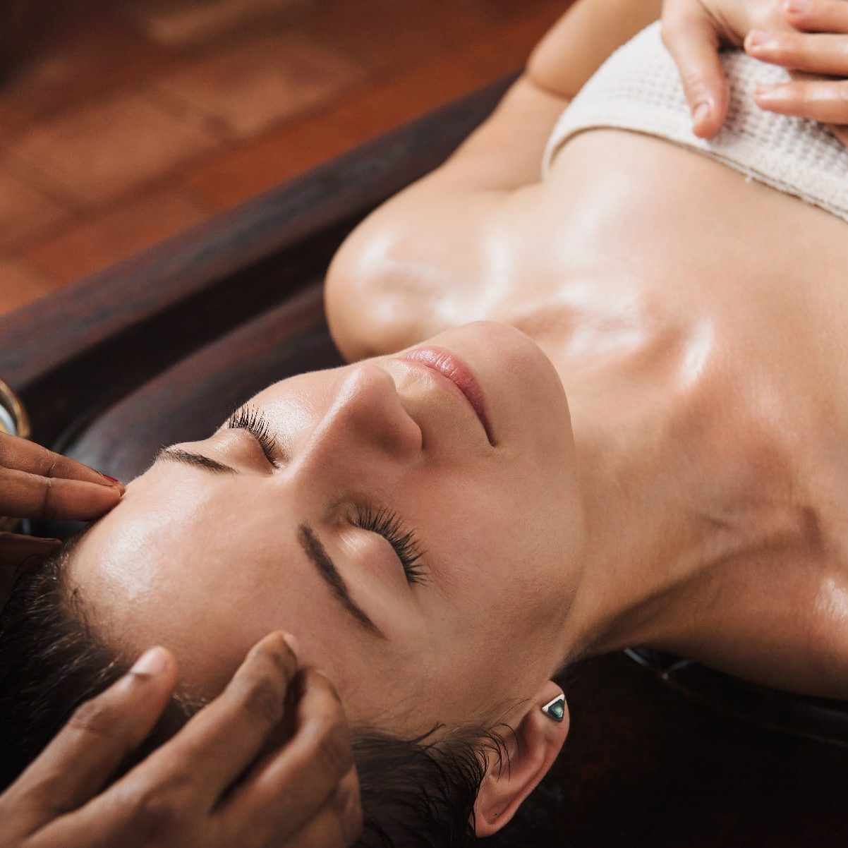Ayurvedic face massage with oil on the wooden table in traditional style made by asian women.